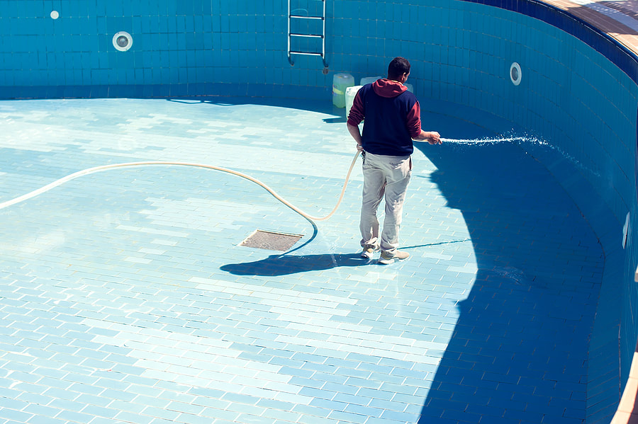 man cleaning the drain pool